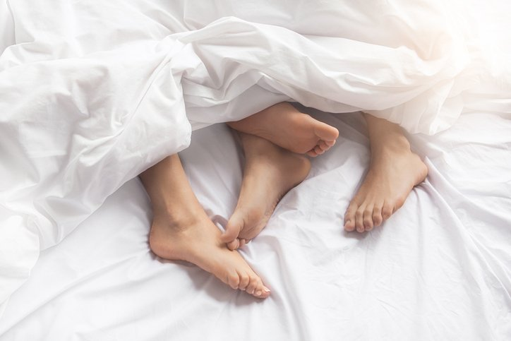 Couple échangiste dans un lit.